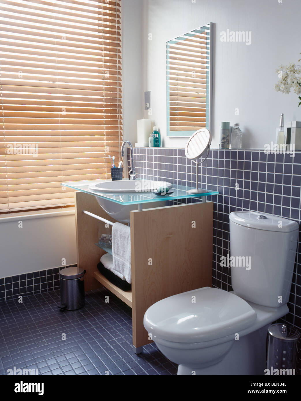 Modern black tiled bathroom with basin in glass and wood vanity ...