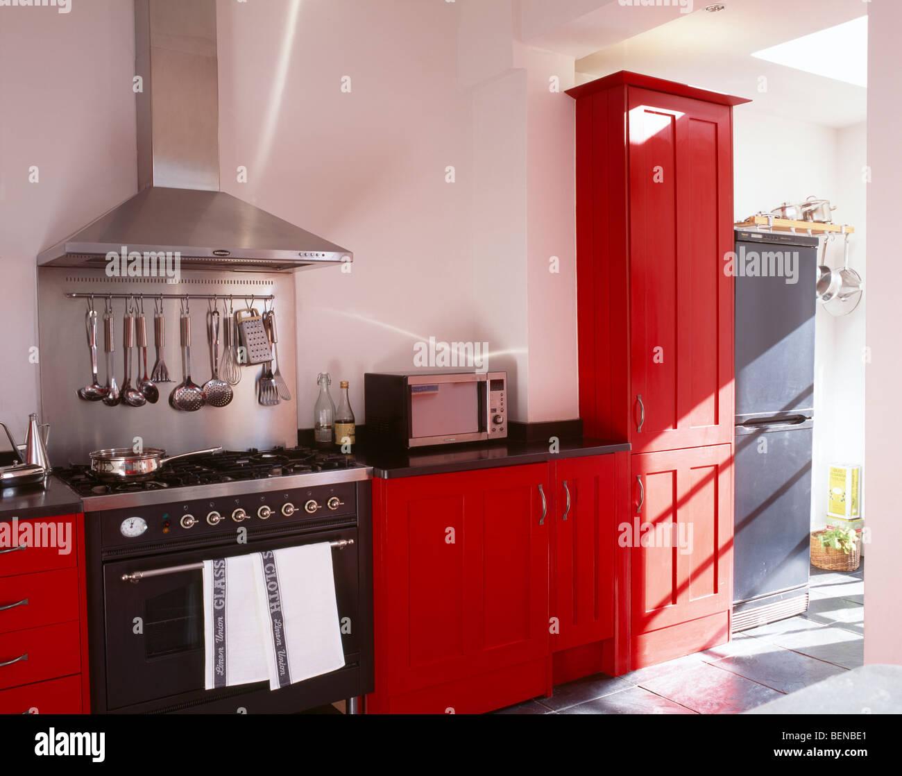 White Kitchen Red Splashback stainless steel extractor and splash-back above black range oven