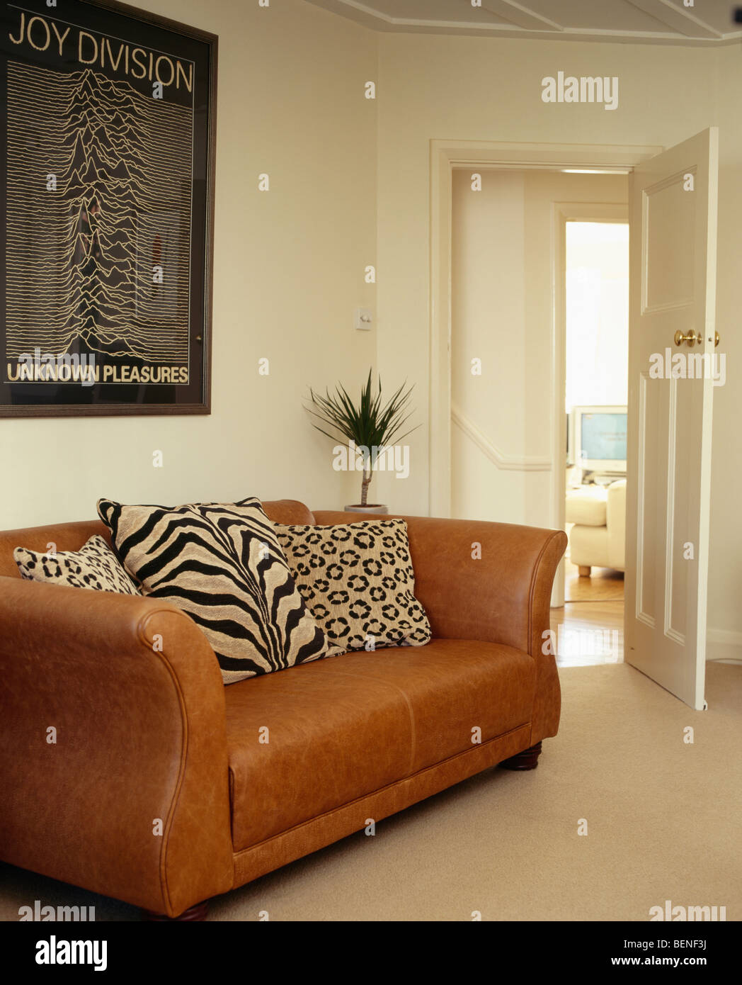 Tiger And Leopard Print Cushions On Brown Leather Sofa In Modern Cream  Living Room