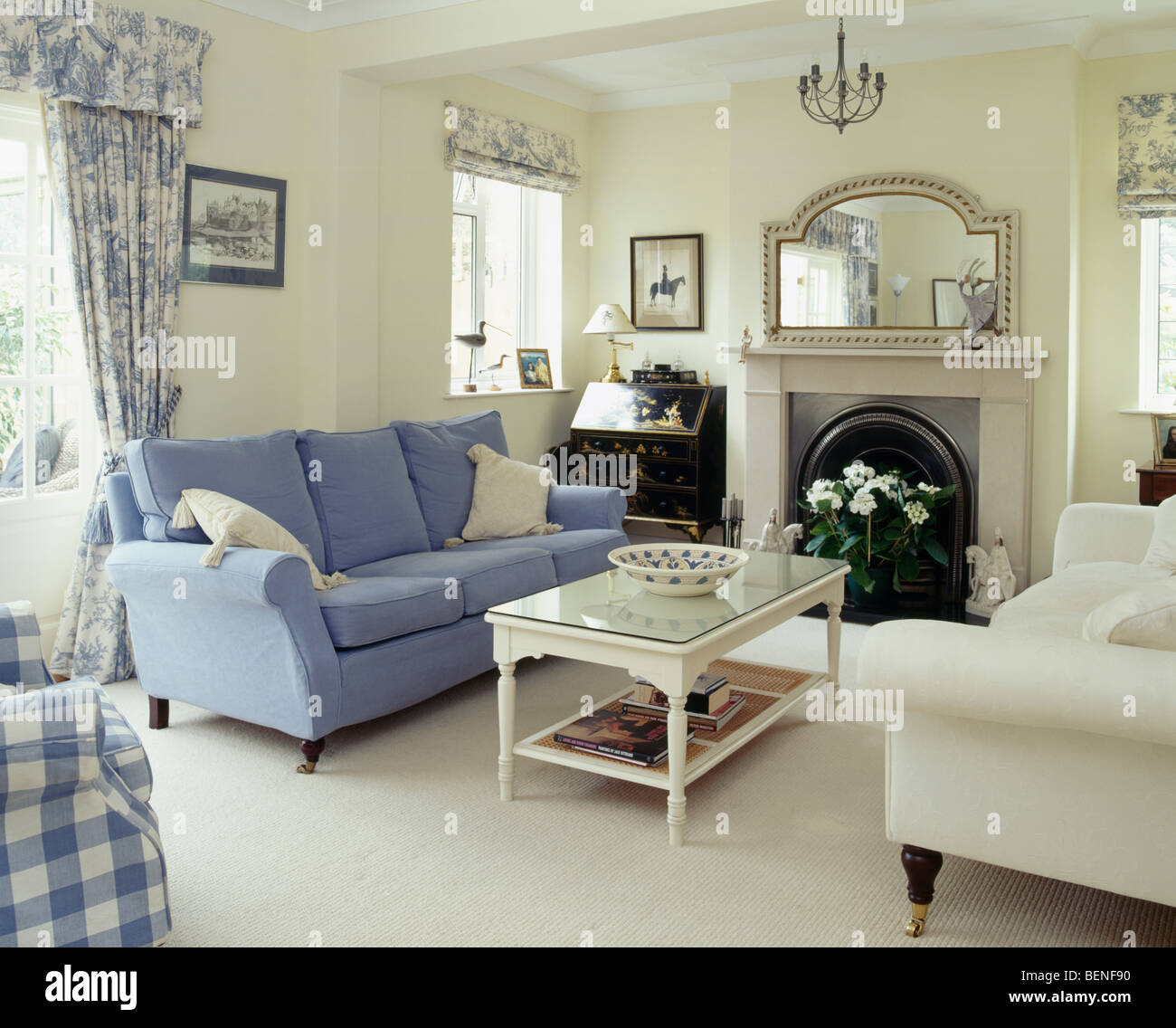 Blue and cream sofas on either side of fireplace in cream living