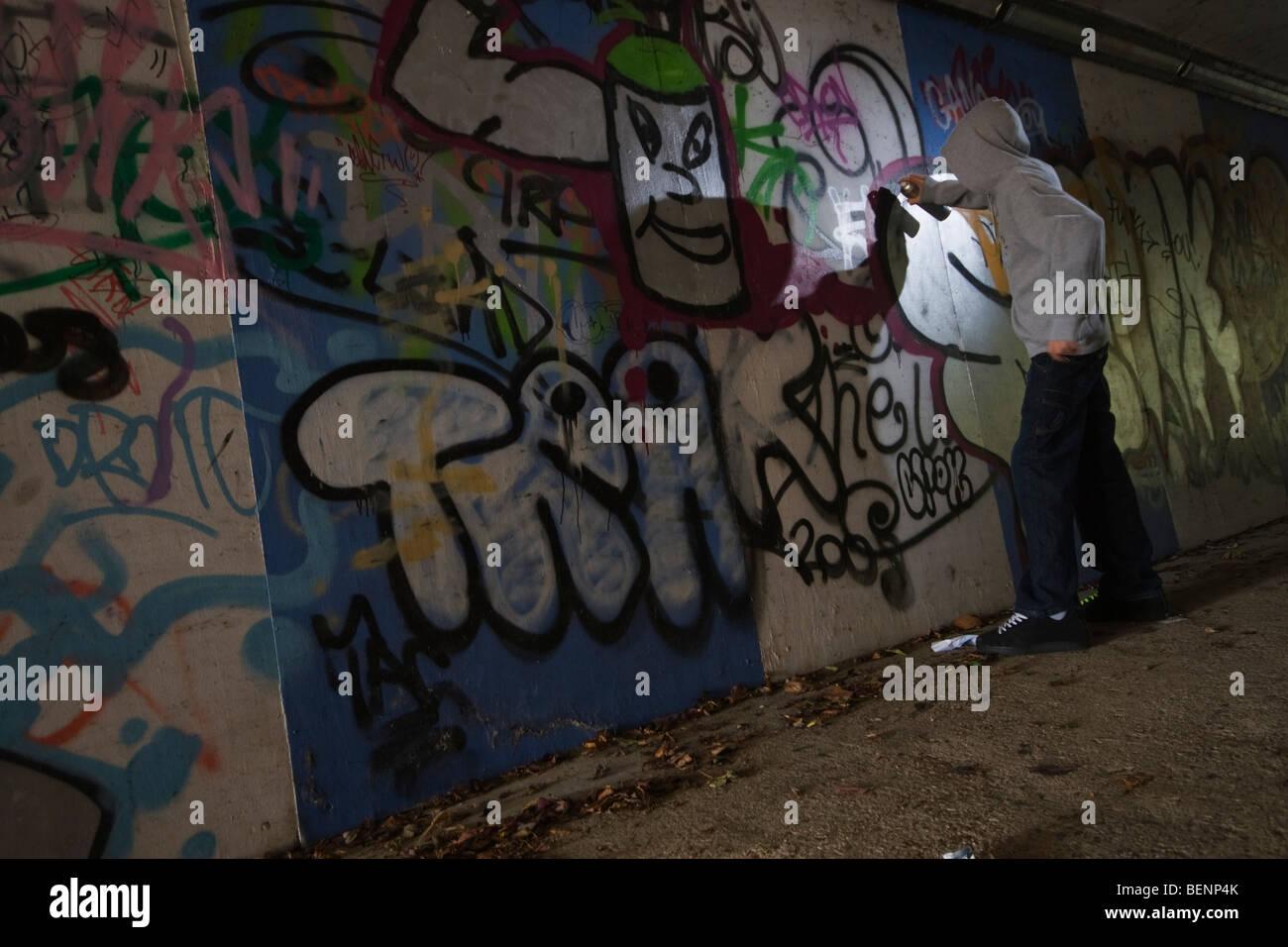 Graffiti wall chelmsford - A Teenage Boy Spraying Graffiti On A Wall In An Alley Stock Image