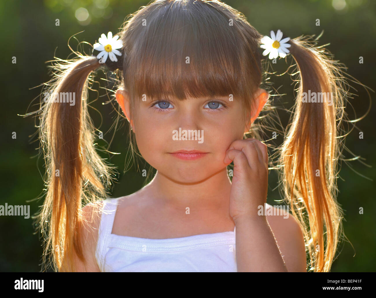 Portrait Of Beautiful Little Girl In Pigtail And Daisy