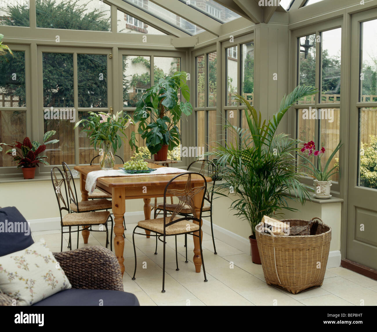 Wooden table and metal chairs in large conservatory dining room ...