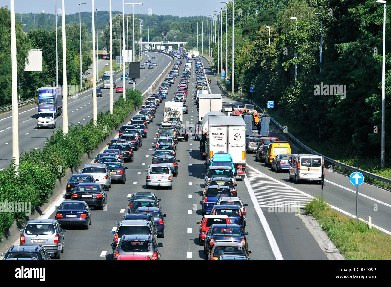 Cars and trucks queueing in highway lanes at approach slip road ...
