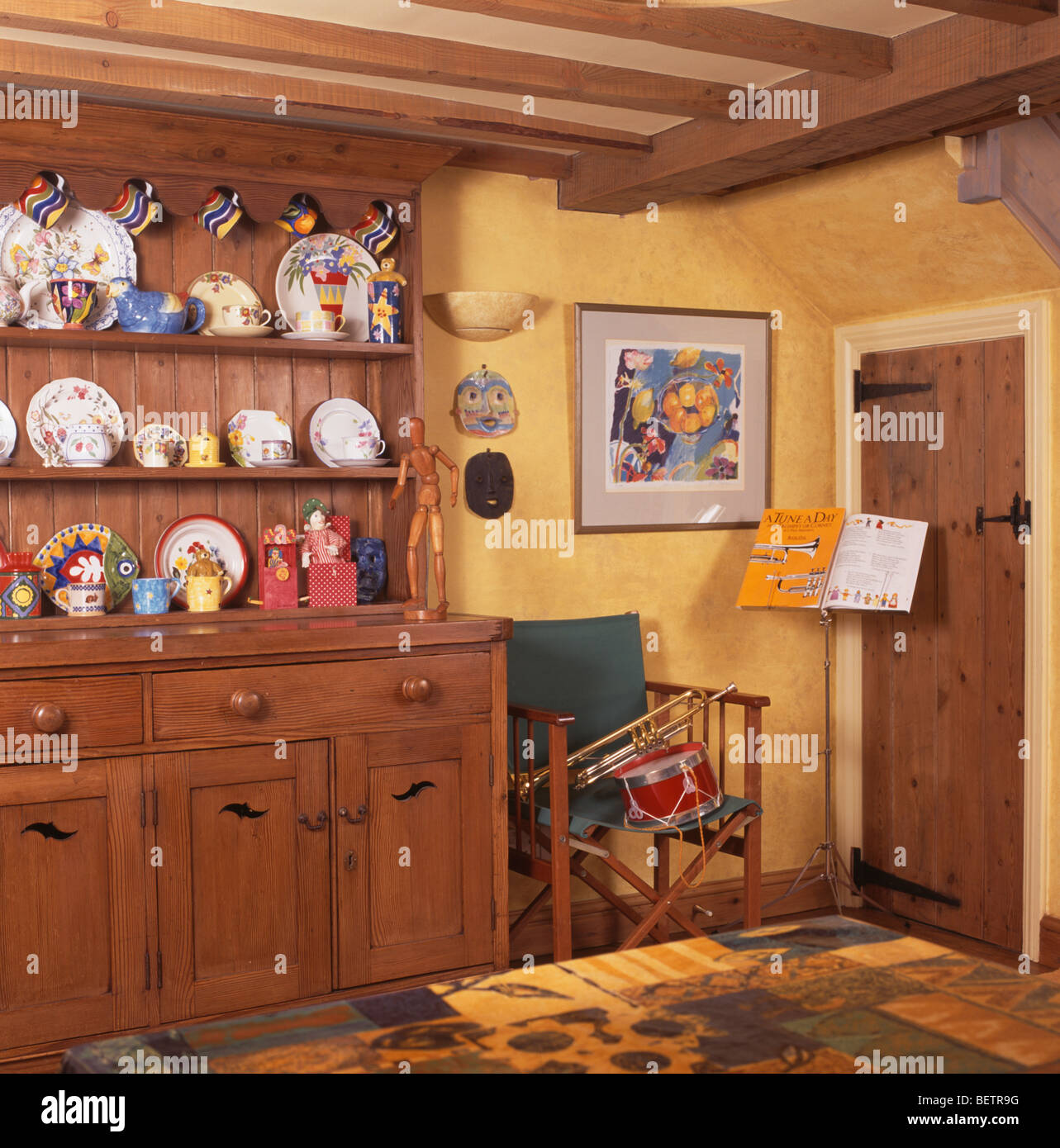 Pine Dresser In Yellow Cottage Dining Room With Music Stand Beside Directors Chair Corner Of The