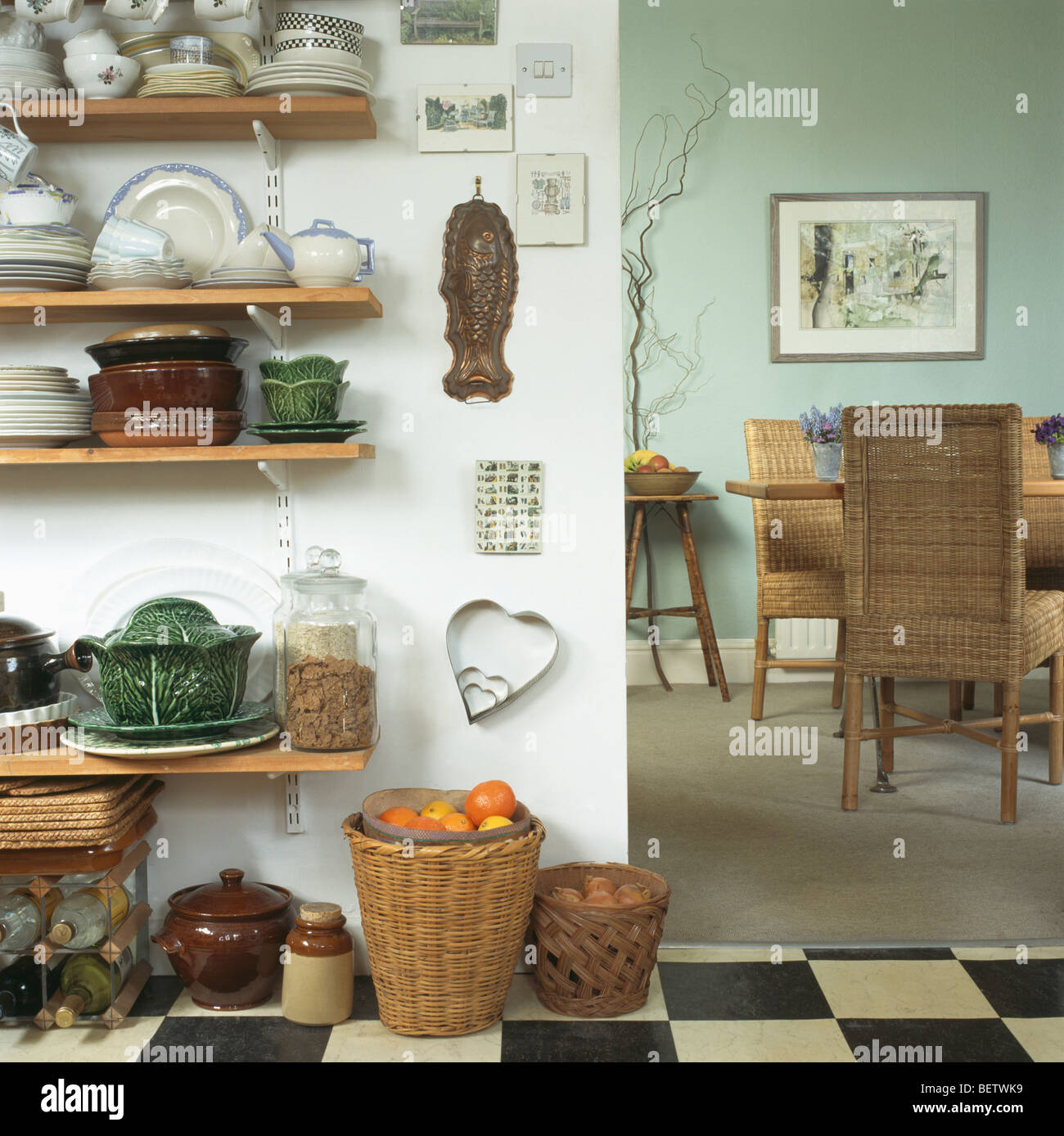 Crockery On Wooden Kitchen Shelves Beside Doorway To Dining Room With Tall Back Wicker Chairs