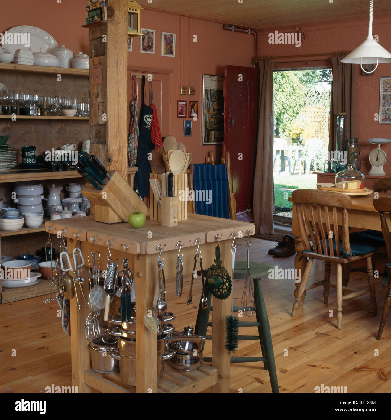 Metal Utensils On Hooks Butchers Block In The Centre Of Large Country Kitchen Dining Room With Wooden Flooring