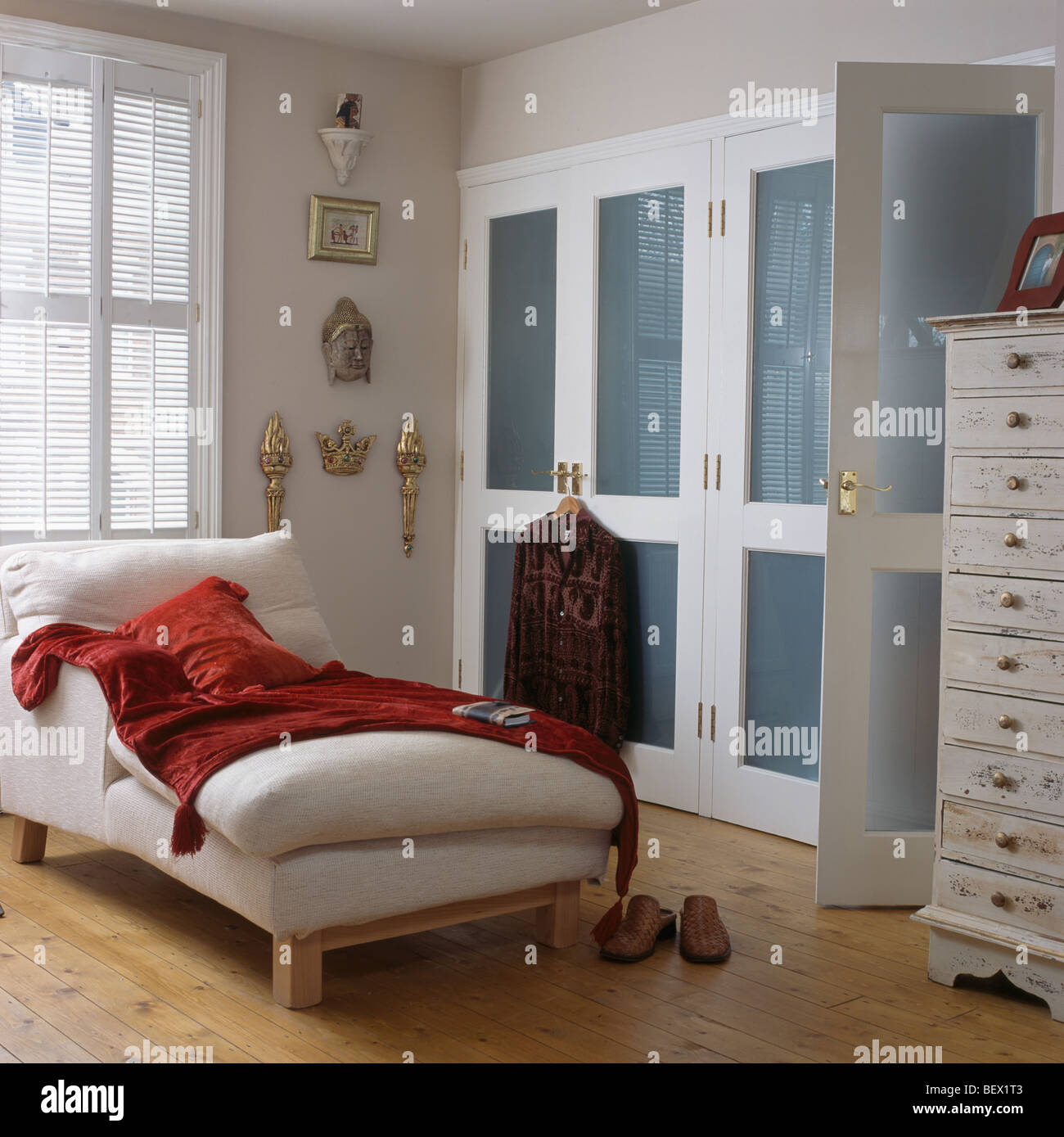 Chaise For Bedroom. Red velvet throw on white chaise longue in townhouse bedroom with  blue fitted wardrobe and wooden flooring