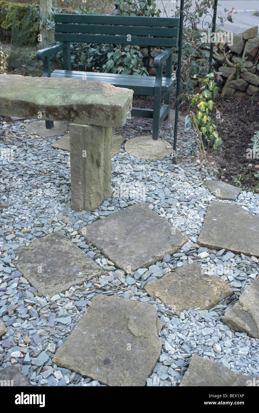 Rustic Stone Table And Metal Bench On Gravel Patio With Stone Paving Slabs  In Small Front Garden