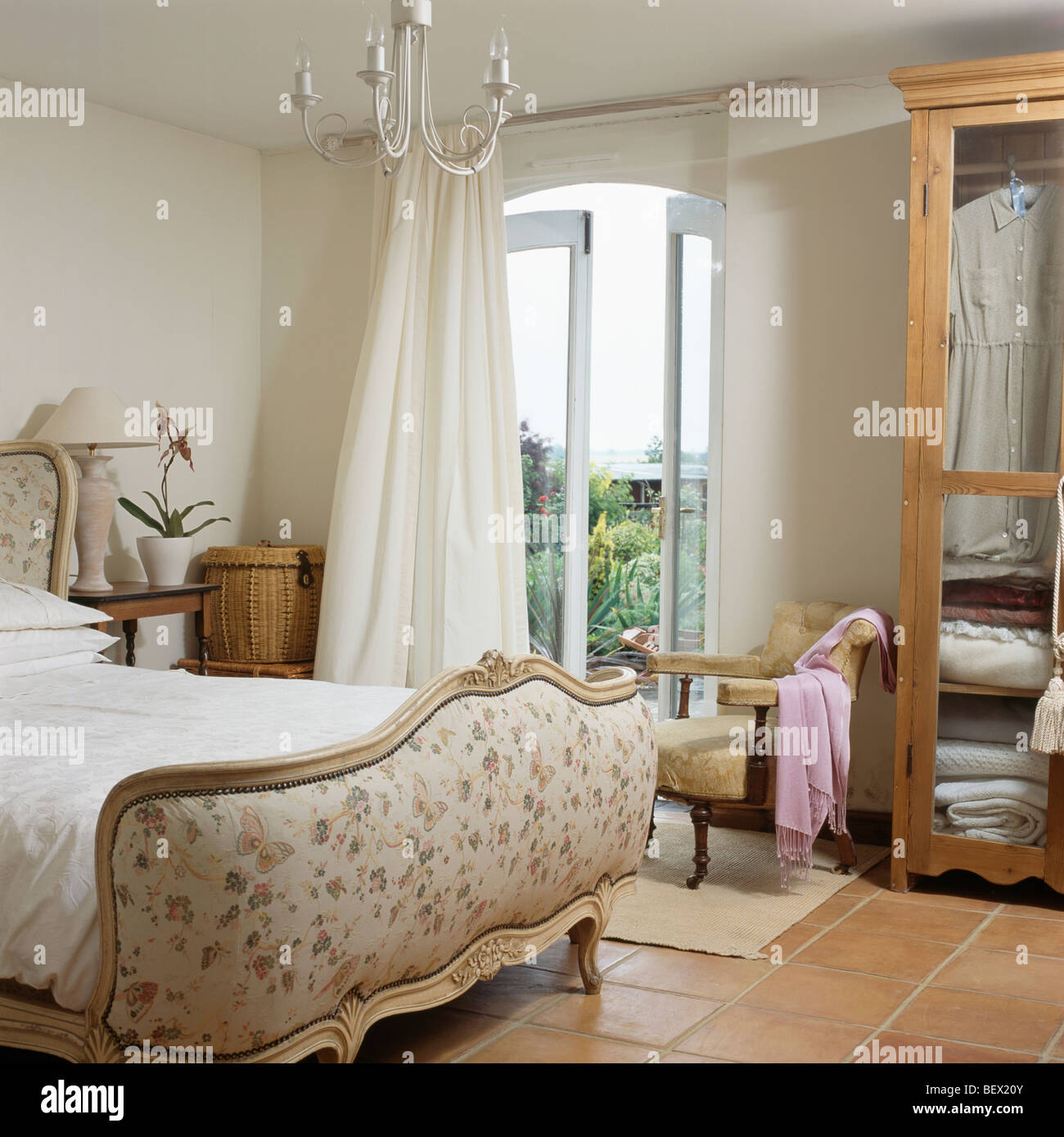 Stock Photo   Upholstered French bed in cream country bedroom with cream  curtains at French windows with view of the garden. Upholstered French bed in cream country bedroom with cream