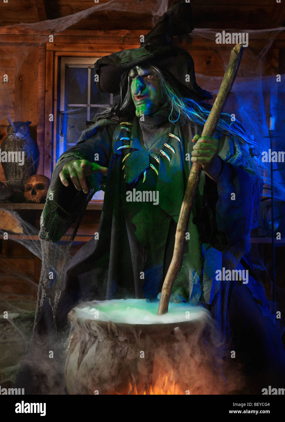 Scary old witch stirring potion in a cauldron inside her ...