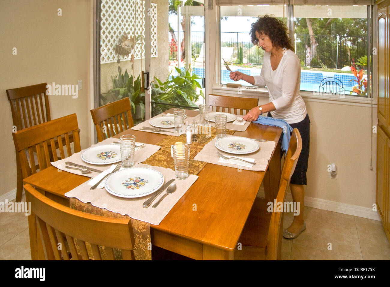 A 50 Year Old Woman Sets Dining Table For Luncheon Guests In Mission Viejo California