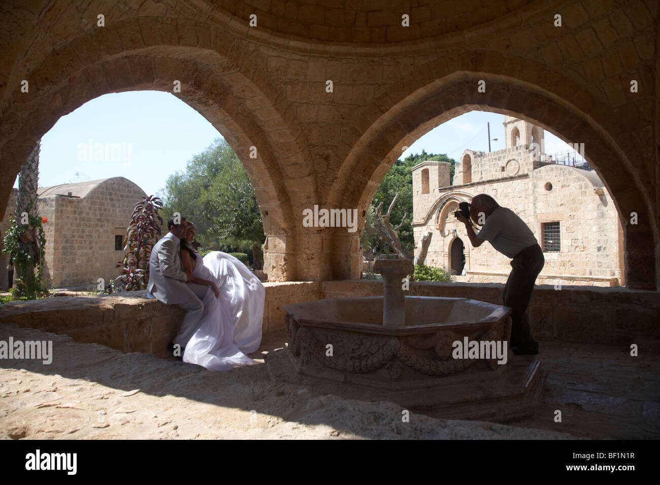 stock photo wedding photographer and bride and groom taking photos in ayia napa monastery republic of cyprus