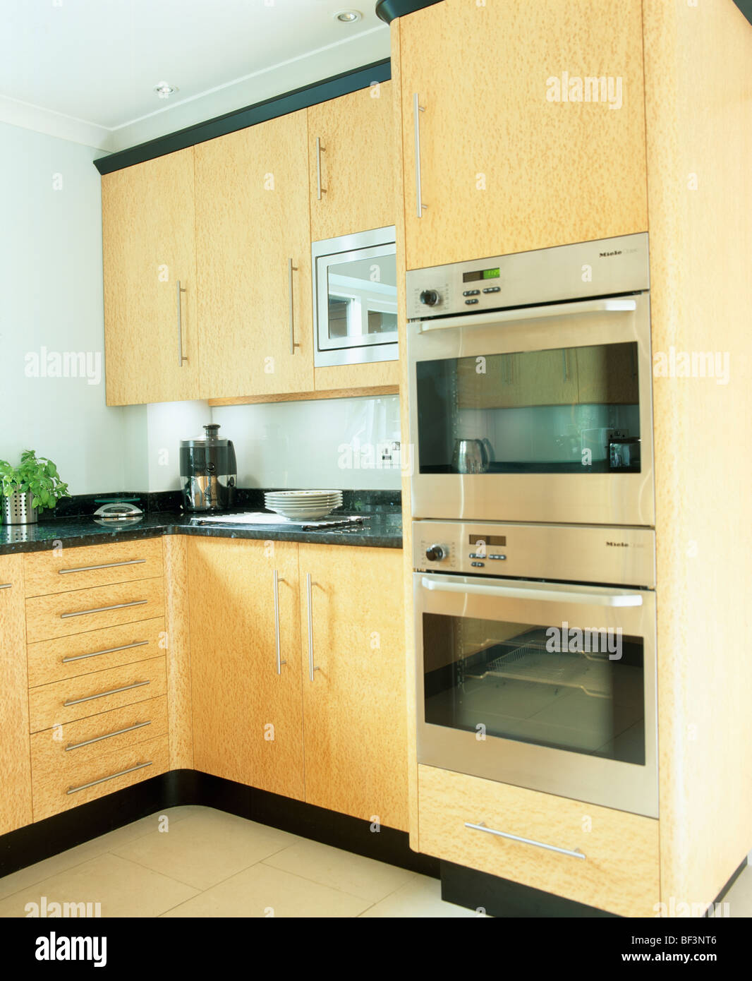 Modern Kitchen Units eye level oven in pale wood unit in modern kitchen with door open