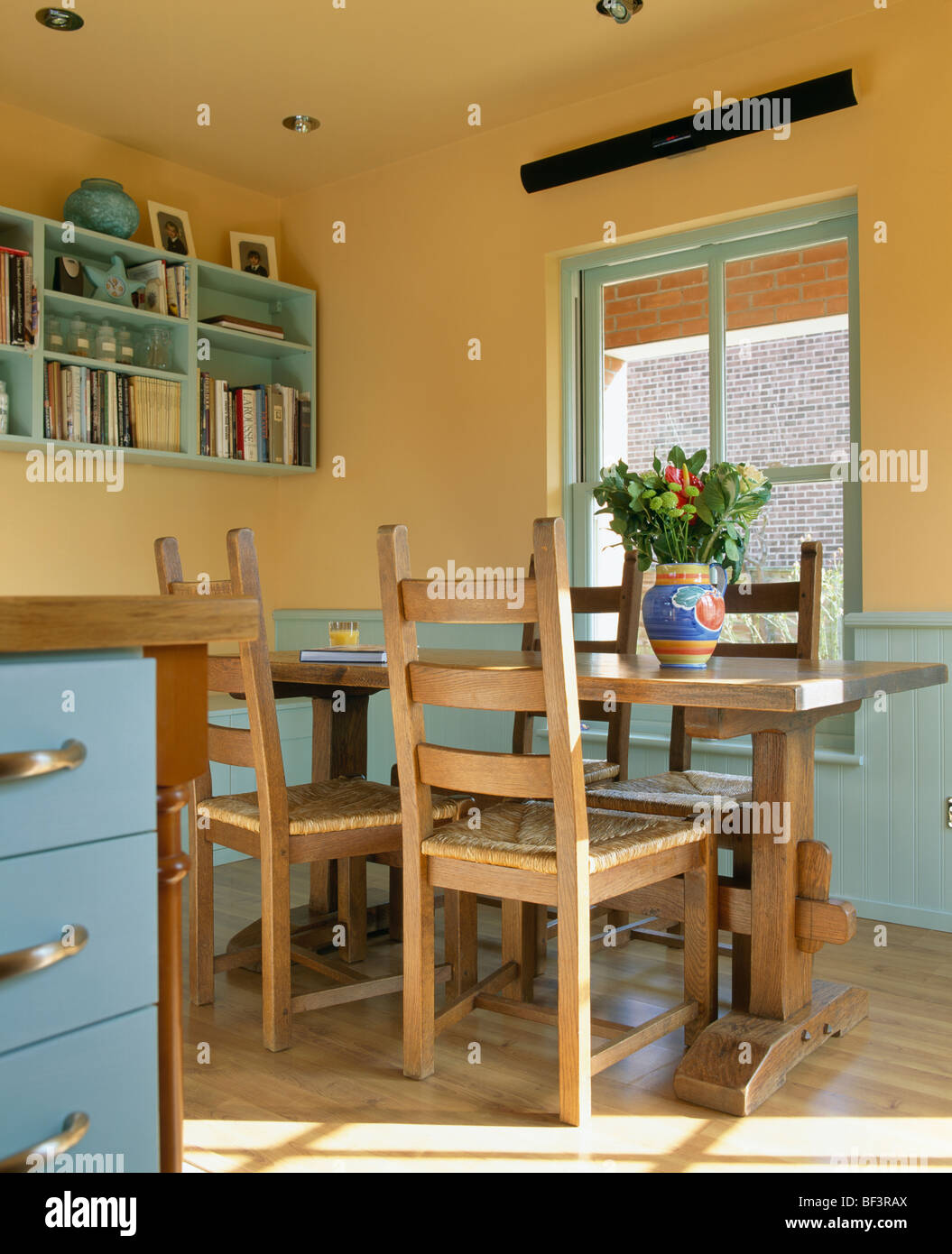 blue and yellow country kitchen. Wooden table chairs in yellow country kitchen with blue dado wall shelves  and panelling Stock