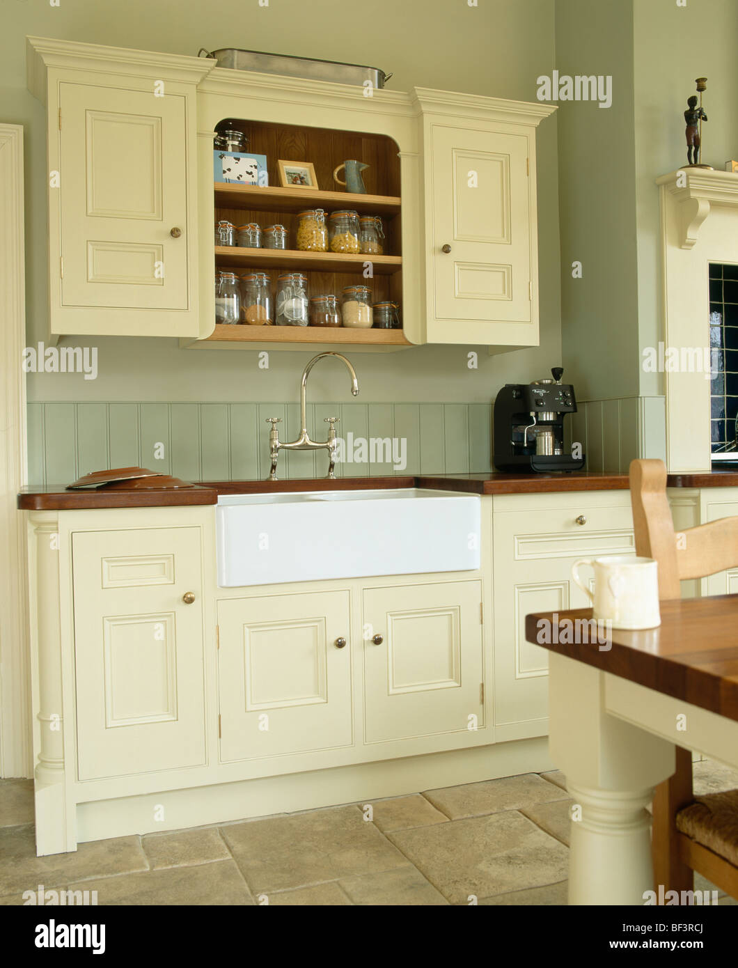 Stock Photo   White Belfast Sink In Cream Fitted Unit Below Fitted Wall  Cupboard In Traditional Country Kitchen Painted In Farrow+Ball Paint