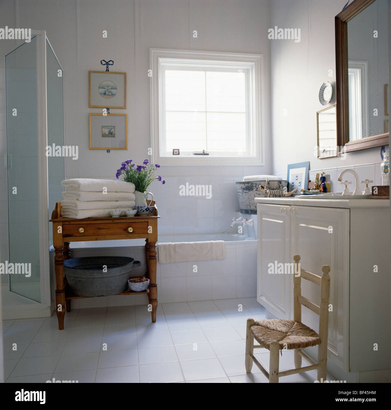 White towels on old pine table in white bathroom with childs white towels on old pine table in white bathroom with childs rush seated chair beside vanity unit geotapseo Choice Image