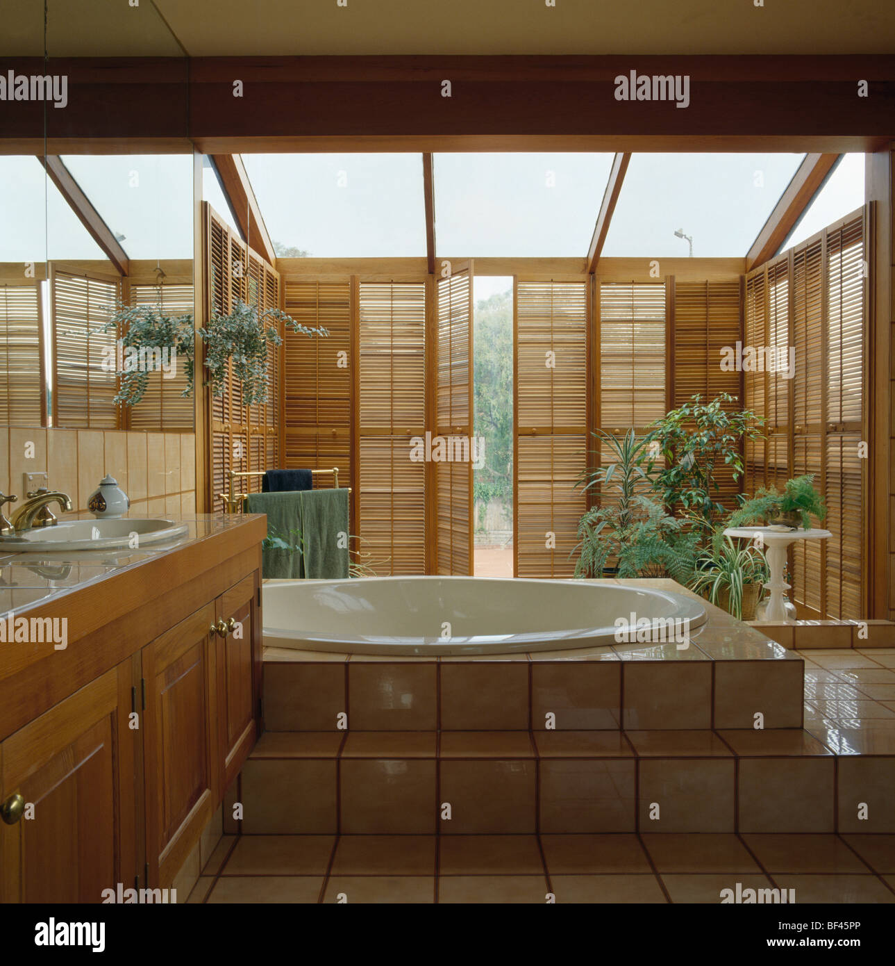 Delightful Wooden Louvre Shutters In Modern Glass Bathroom Extension With Oval Bath