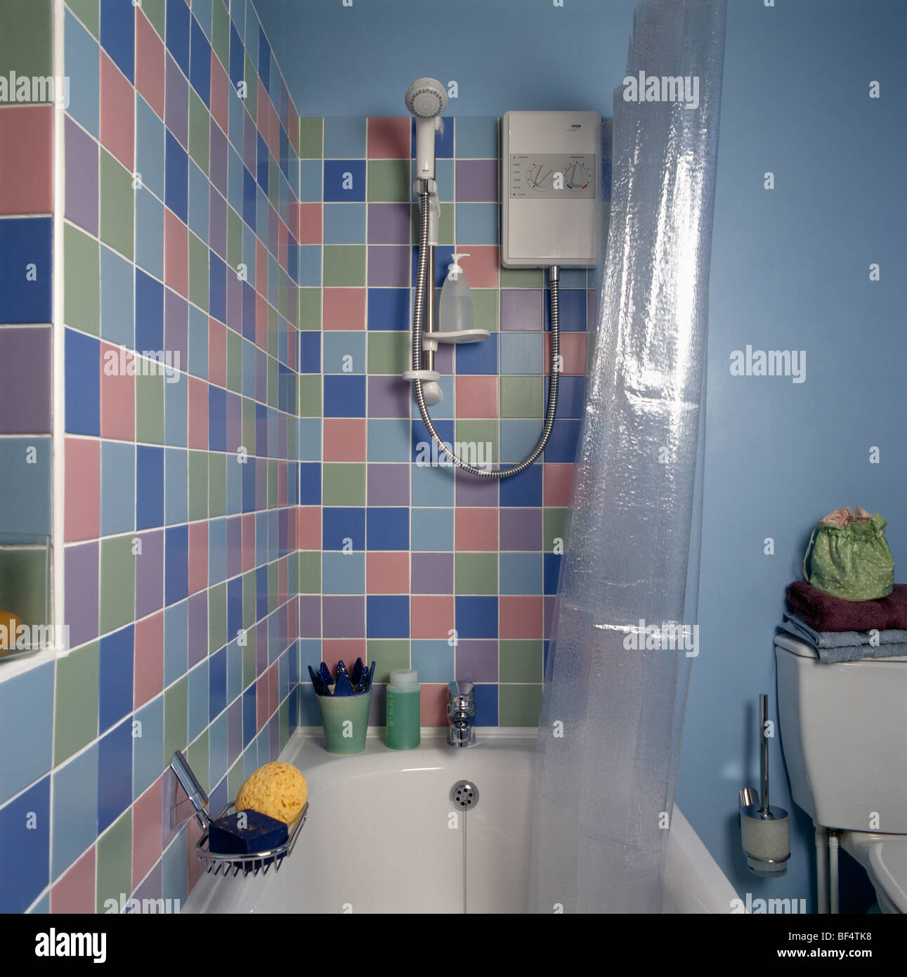 Pastel colored wall tiles above bath with clear plastic Stock ...