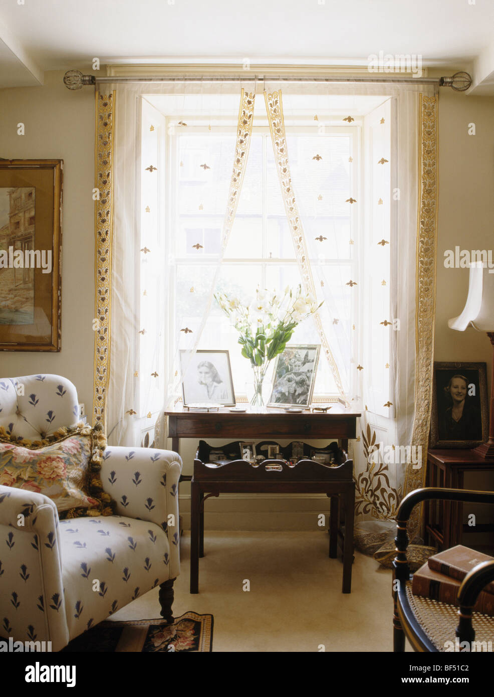 cream patterned armchair in small cottage living room with antique