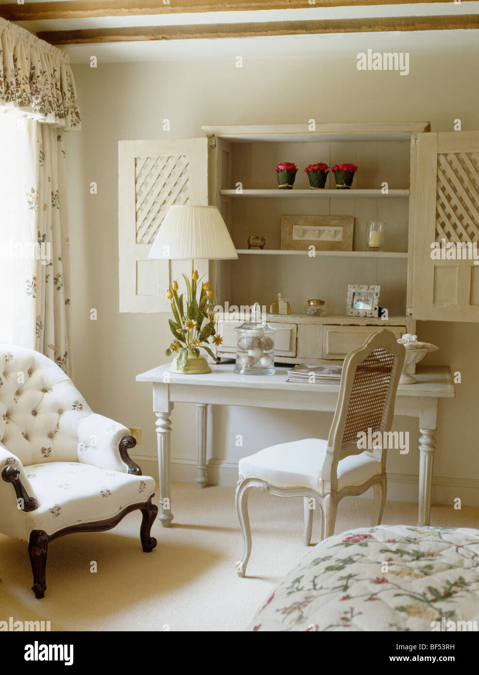 Stock Photo   Wooden Shutters On Alcove Shelving Above Small White Table  And Chair In Cream Cottage Bedroom With White Button Back Armchair