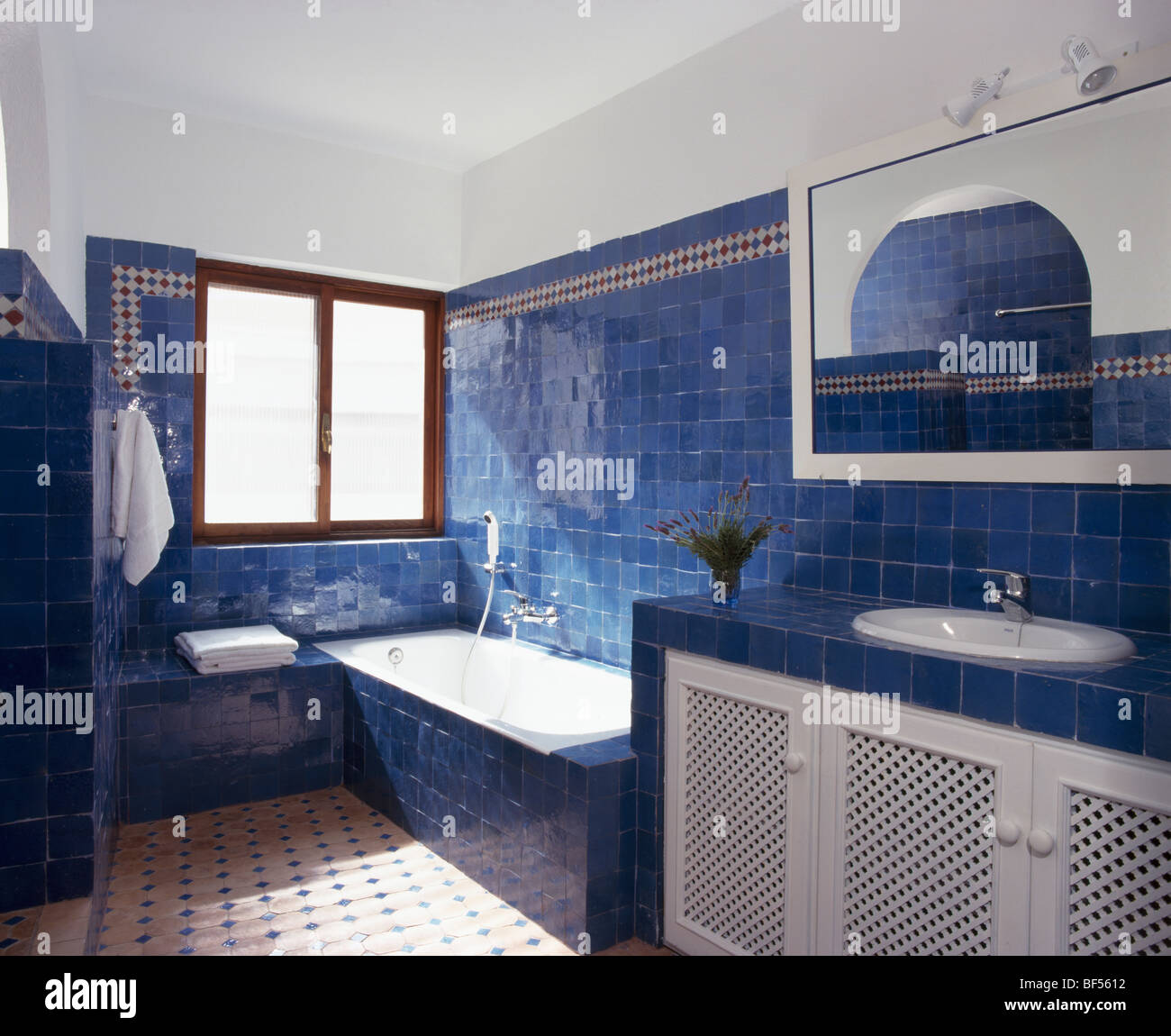 Bright blue tiles on wall above bath in modern Spanish bathroom ...