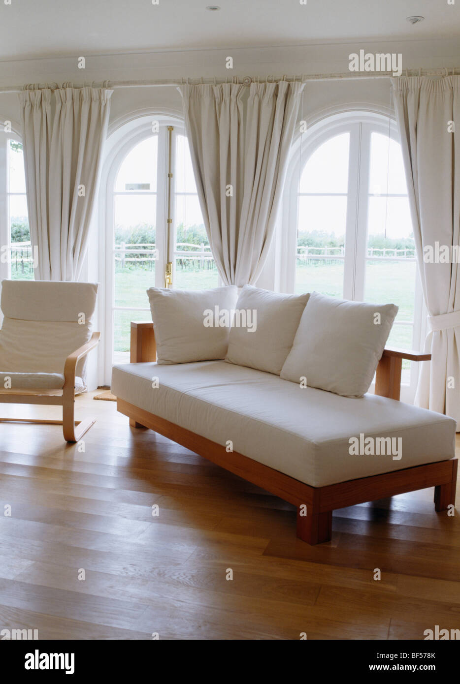 Day Bed With White Cushions In Living Room With Wooden Floor And White  Curtains At French Windows