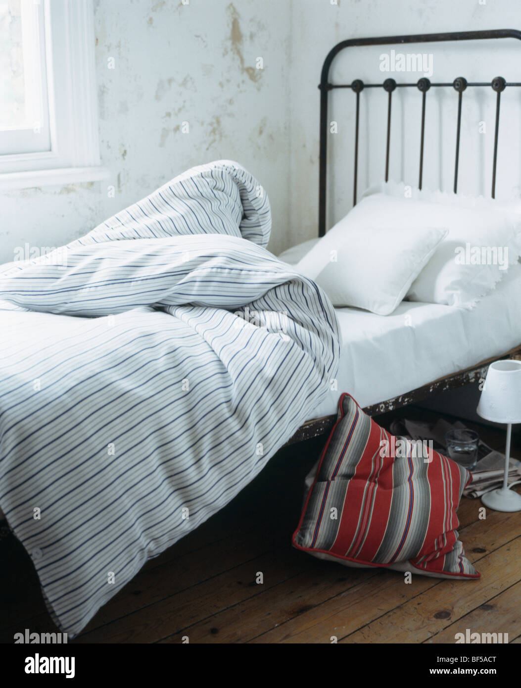 Wrought iron single bed - Stock Photo Striped Duvet On Wrought Iron Single Bed In Cottage Bedroom With White Stone Walls