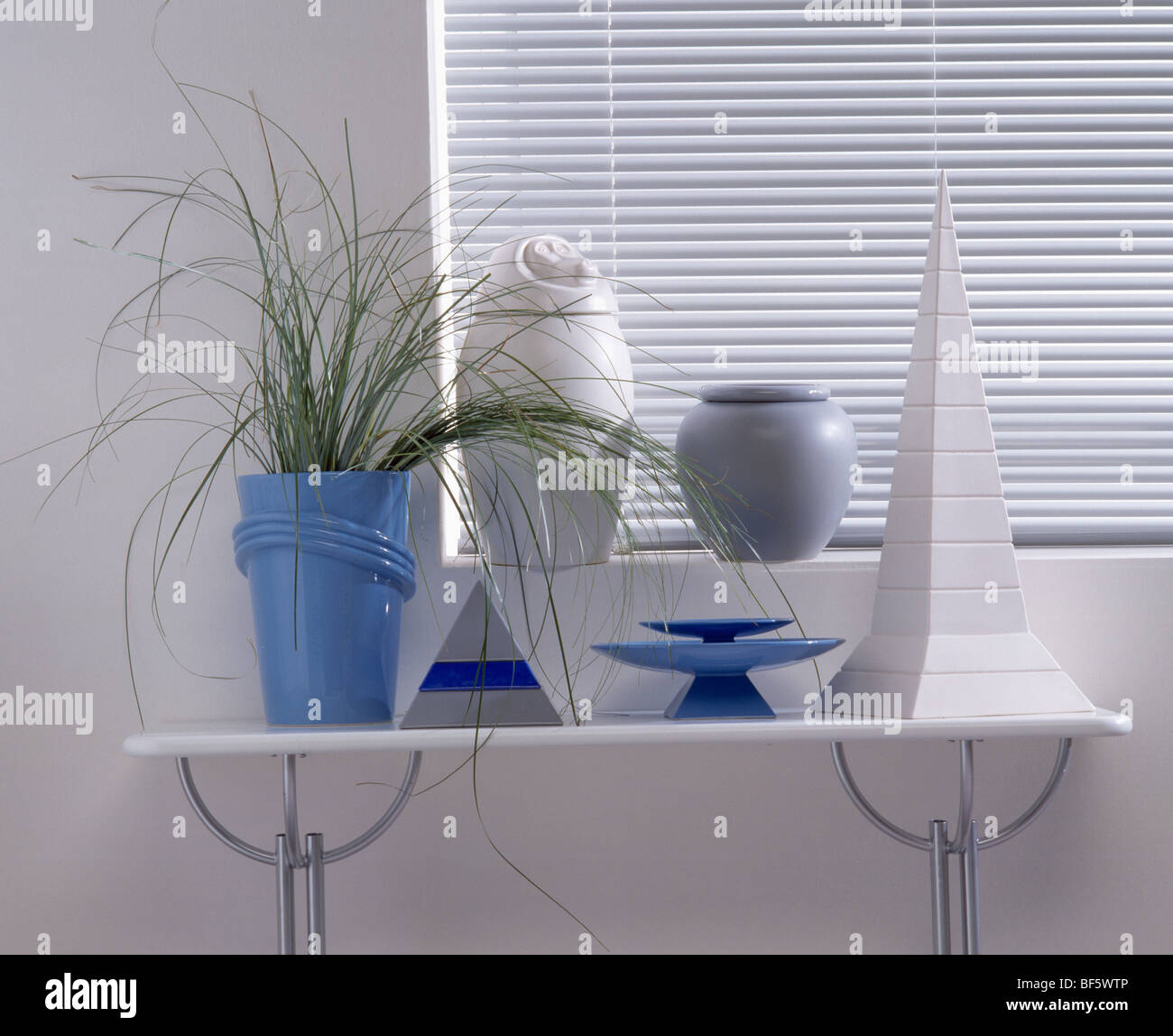 Close Up Of Blue And Silver Vases On Small White Console Table Below Window  With White Venetian Blind