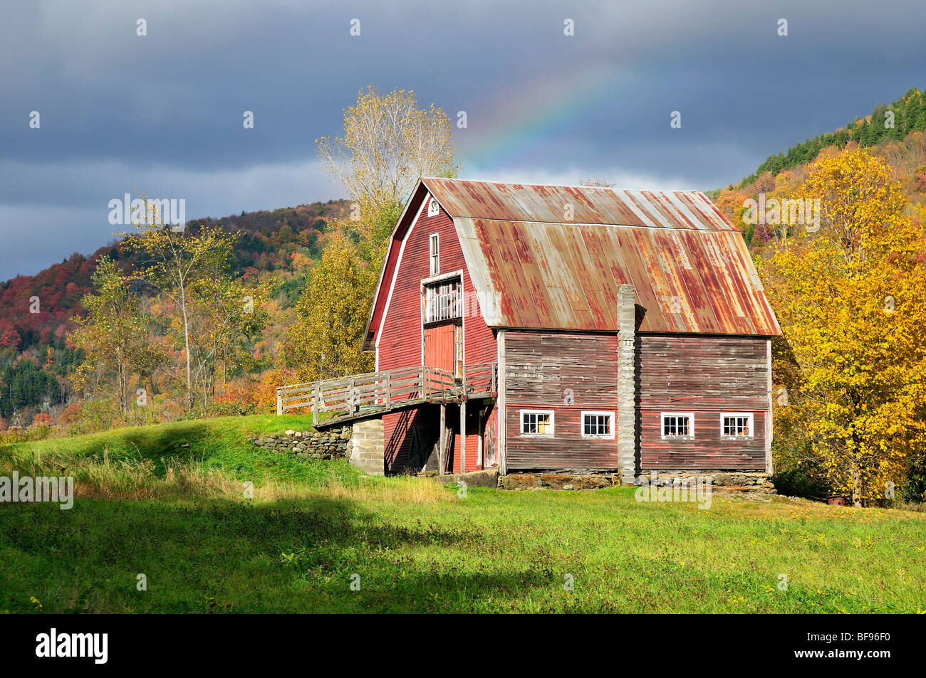 An Old Barn In Vermont With Autumn Foliage Surrounding It Also A Stormy Sky