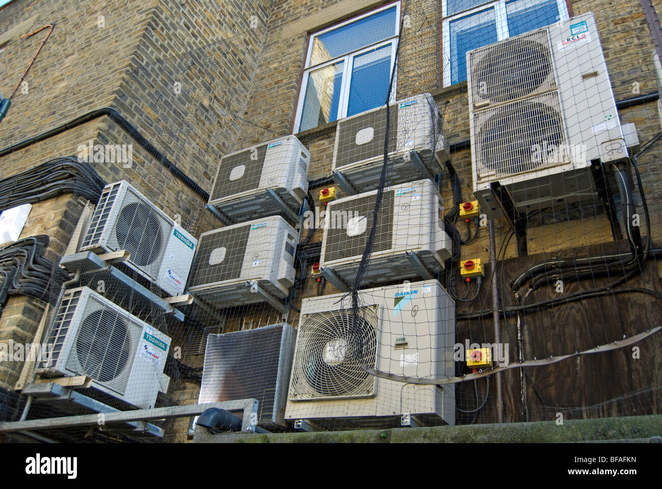 air conditioning machine fans on an exterior wall in a back street