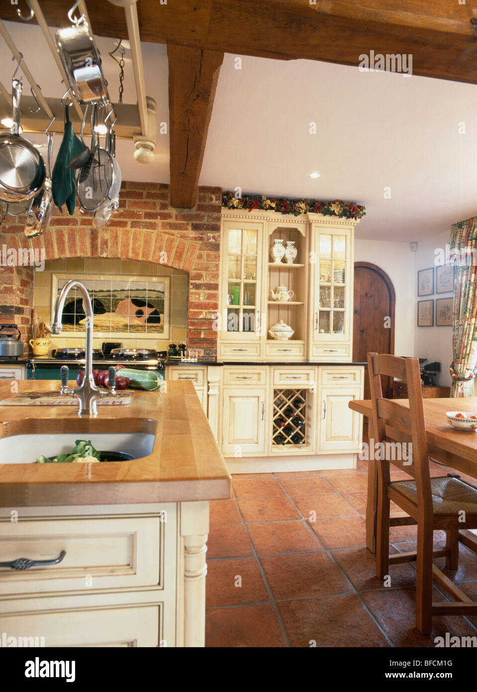 Terracotta Floor Tiles And Exposed Brick Wall In Country Kitchen - Country kitchen tiles