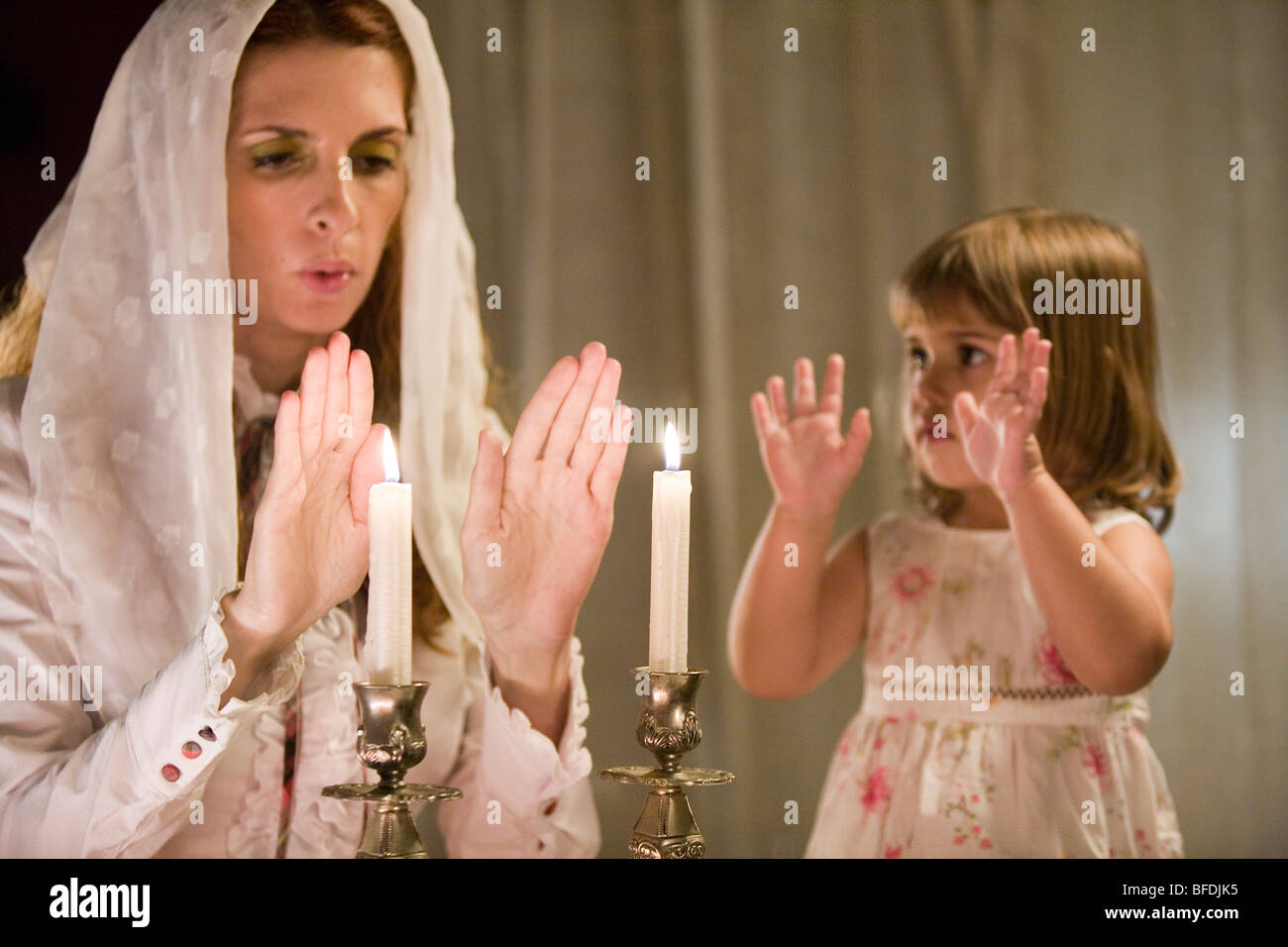 Mother And Daughter Blessing On Shabbat Candles Stock
