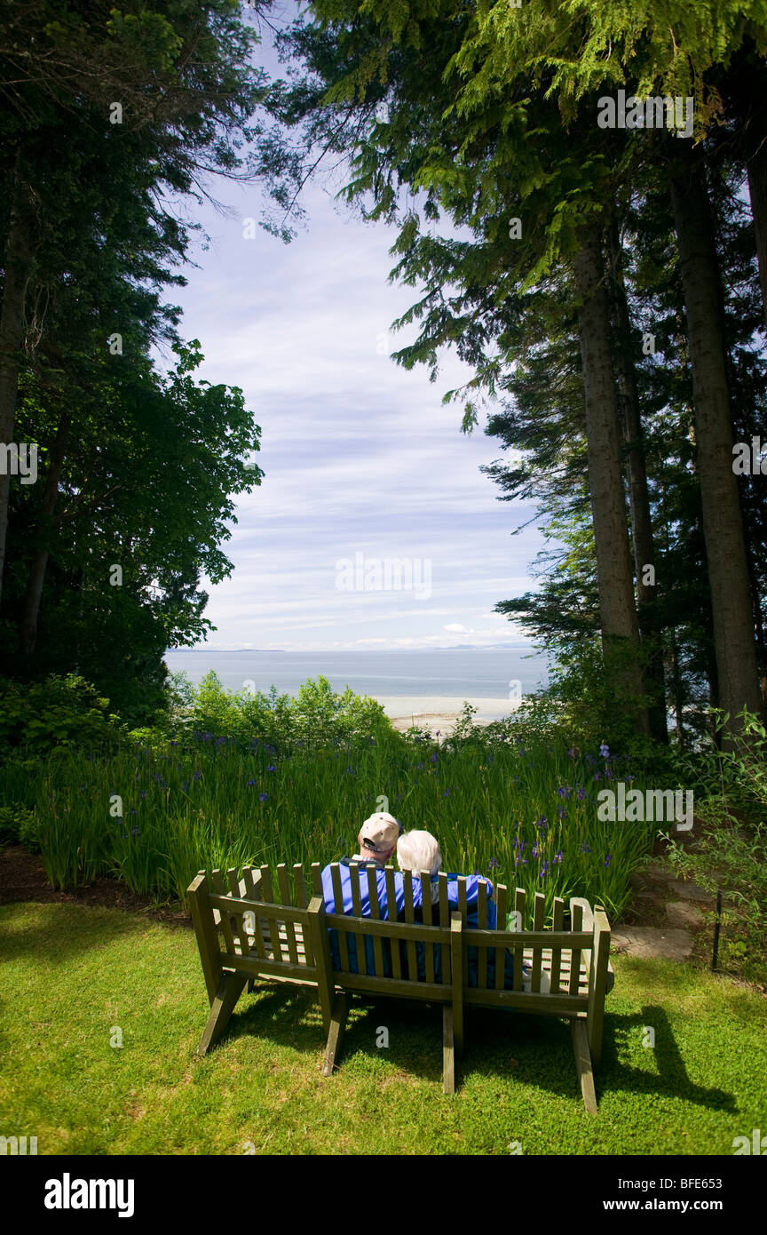 A senior couple sitting on a bench, Qualicum Beach, Vancouver Island ...