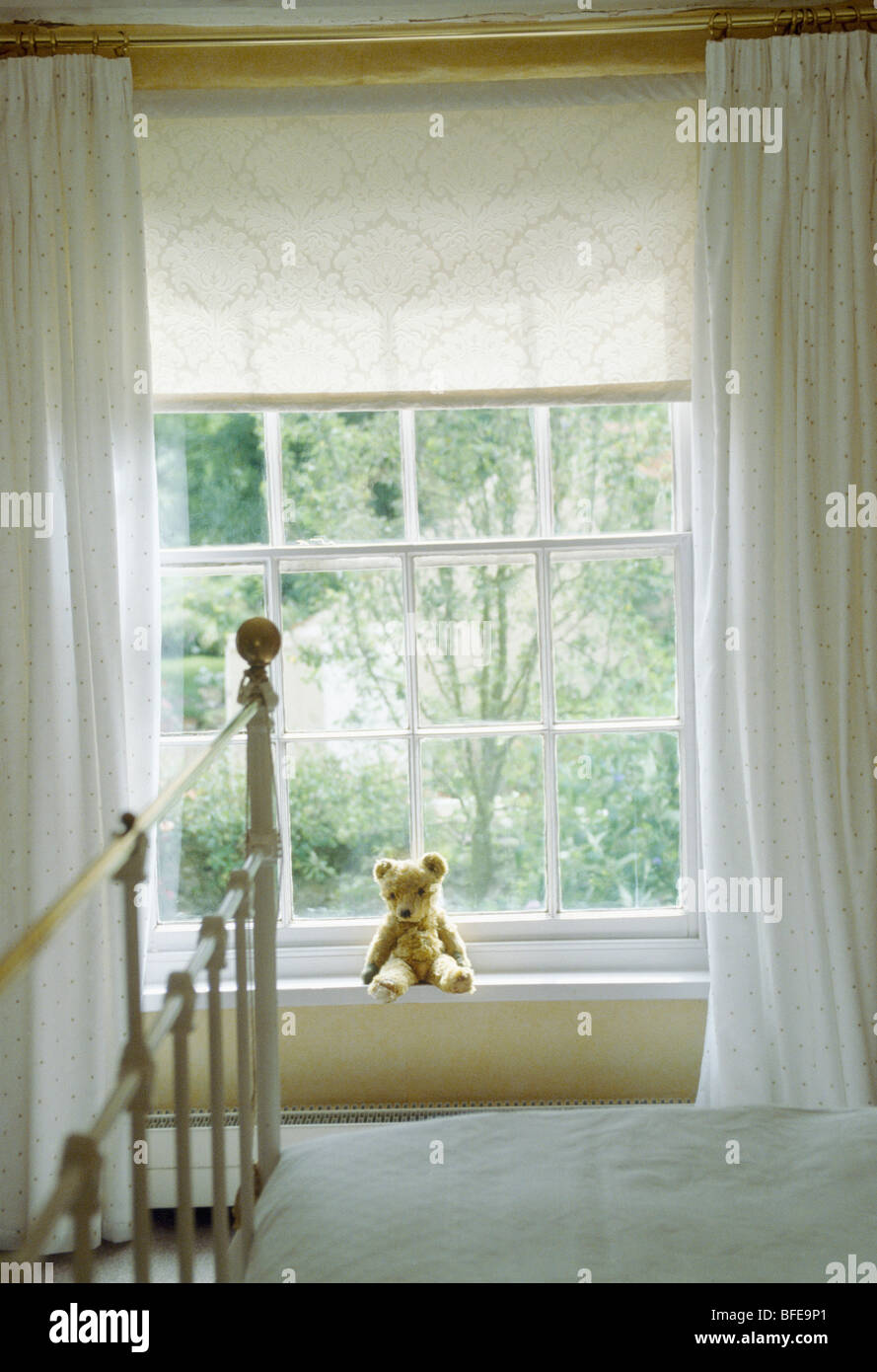 White lace bedroom curtains - Stock Photo Teddy Bear On Window Sill Of Window With Cream Lace Blind And White Curtains In White Country Bedroom With Antique Brass Bed