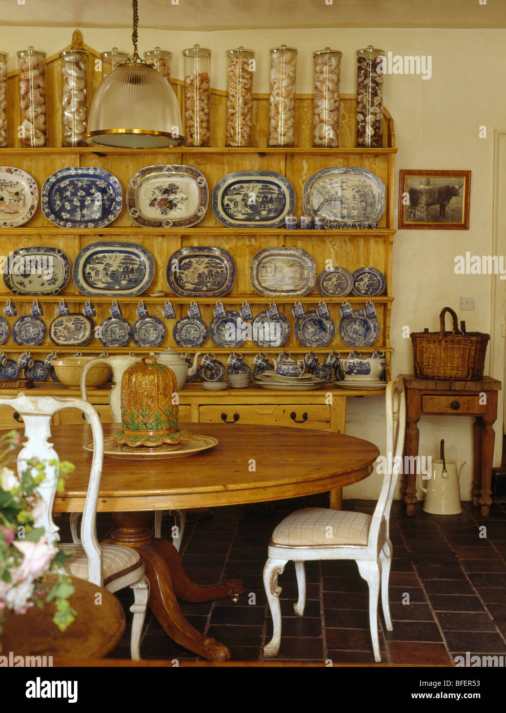 Glass Storage Jars And Blue White Plate Collection On Dresser In Victorian Style Dining Room With Chairs At Pine Table