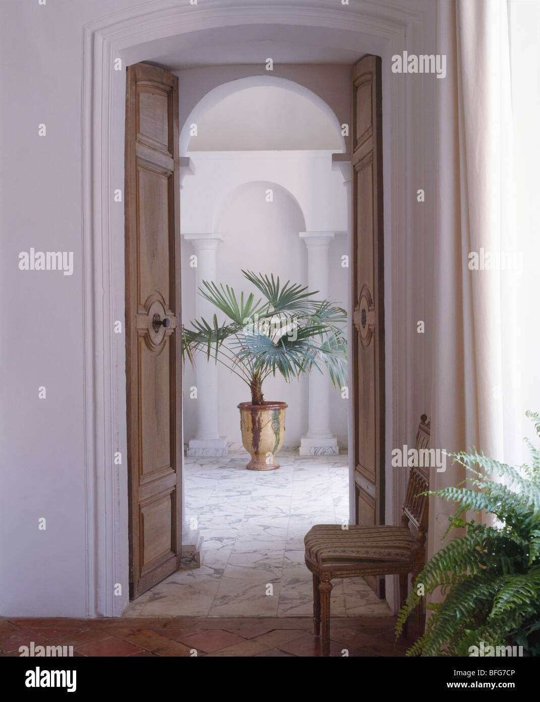 Open double wooden doors in french country hall with for Double open french doors
