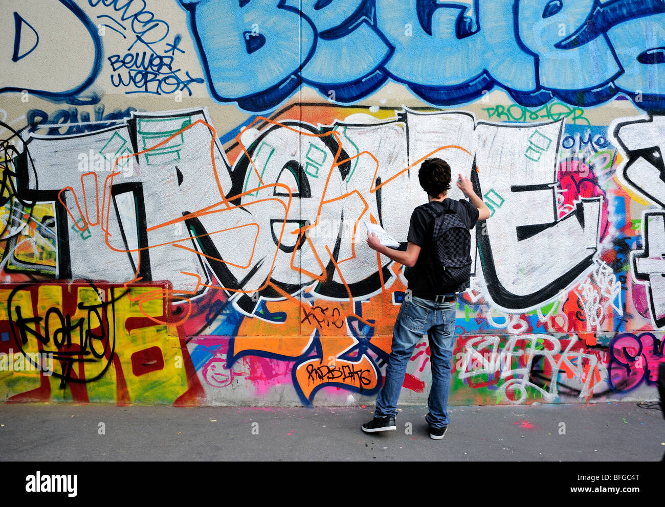 male teen street graffer painting wall with spray paint graffiti. Black Bedroom Furniture Sets. Home Design Ideas