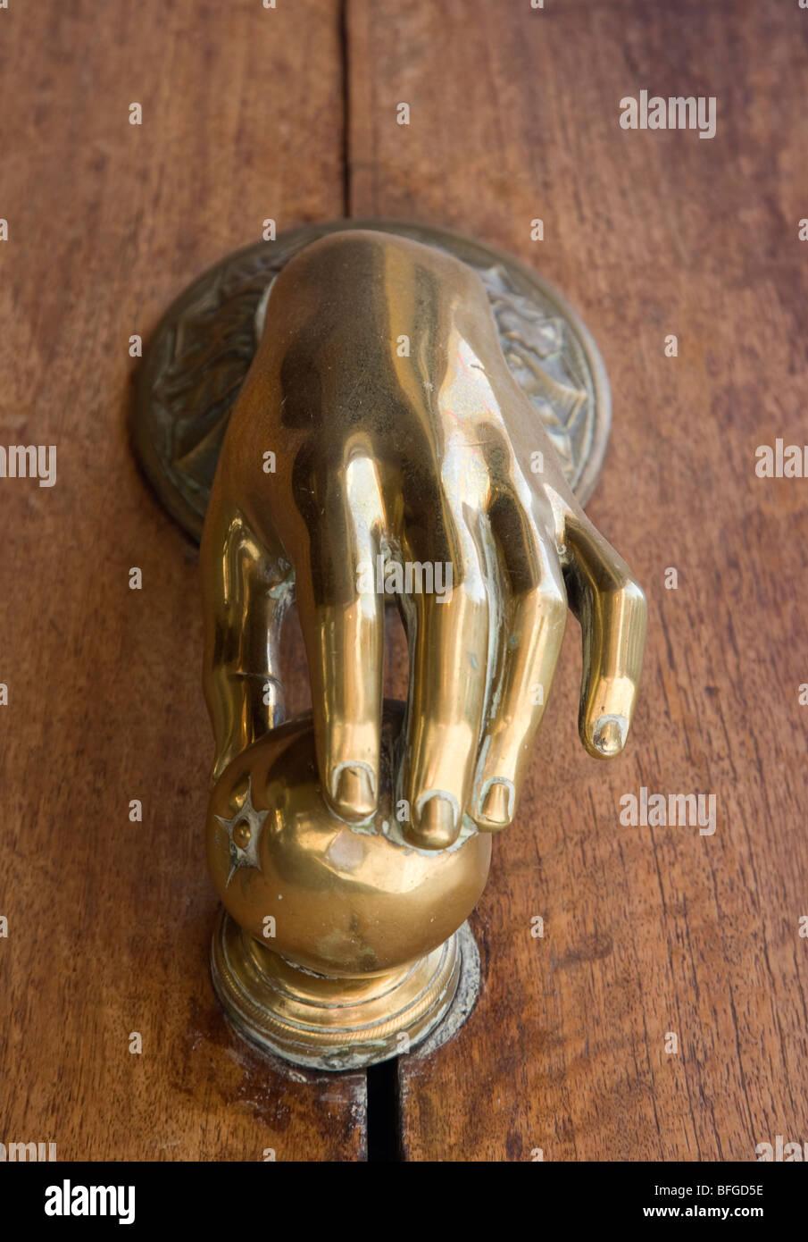 Brass Hand Door Knocker On A Wooden Door