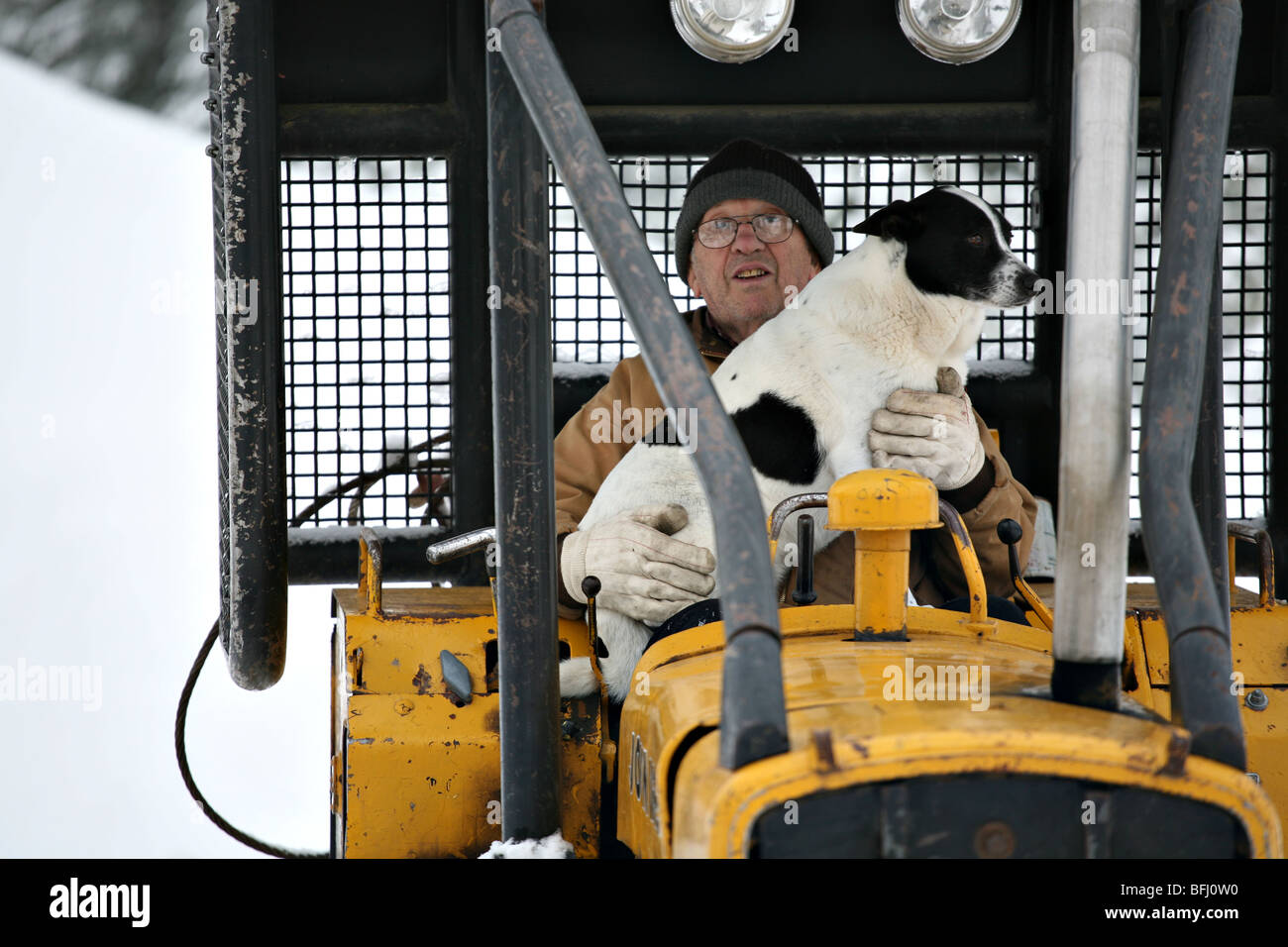 senior citizen and dog sitting in the cab of a bulldozer excavator