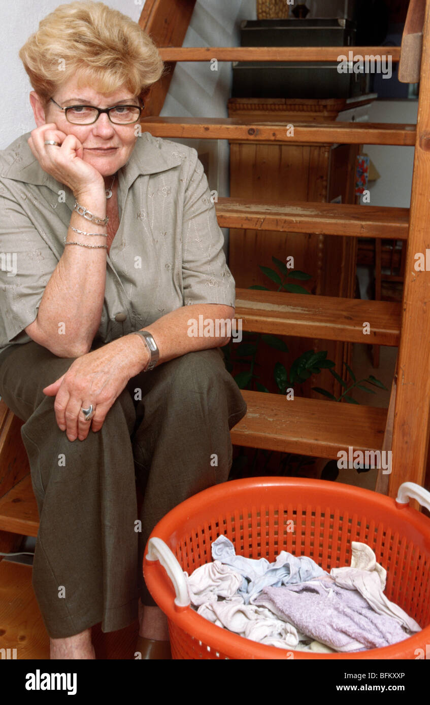 Depressed Woman Resting With Laundry Basket On Stairway   One Only   Woman  Sad One Person Only Indoors