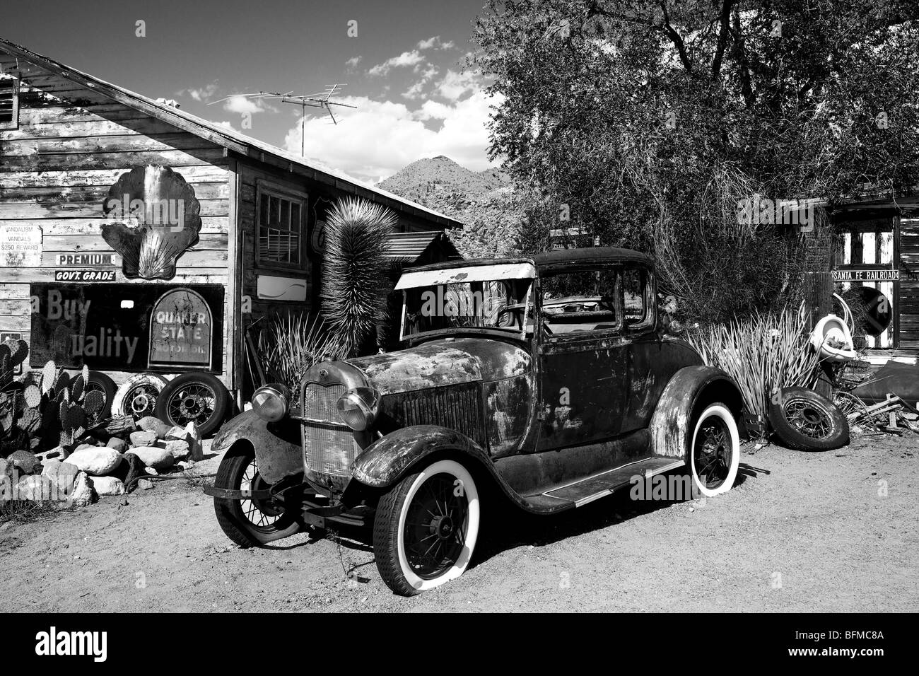 Old looking black and white photo of an old worn car wreck in a ...