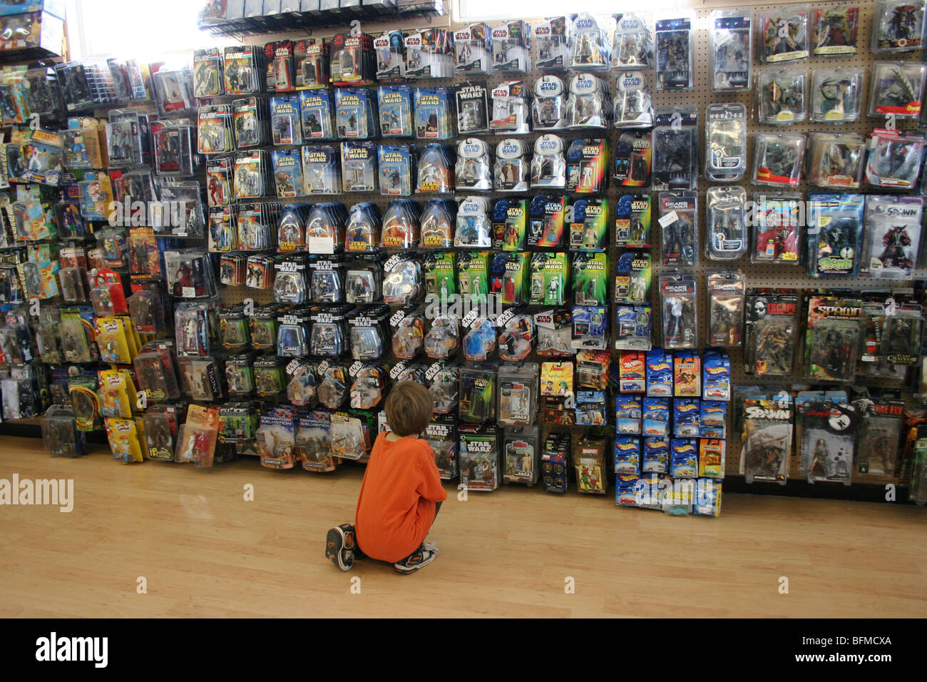 child looking at assorted action figure toys at a toy ...