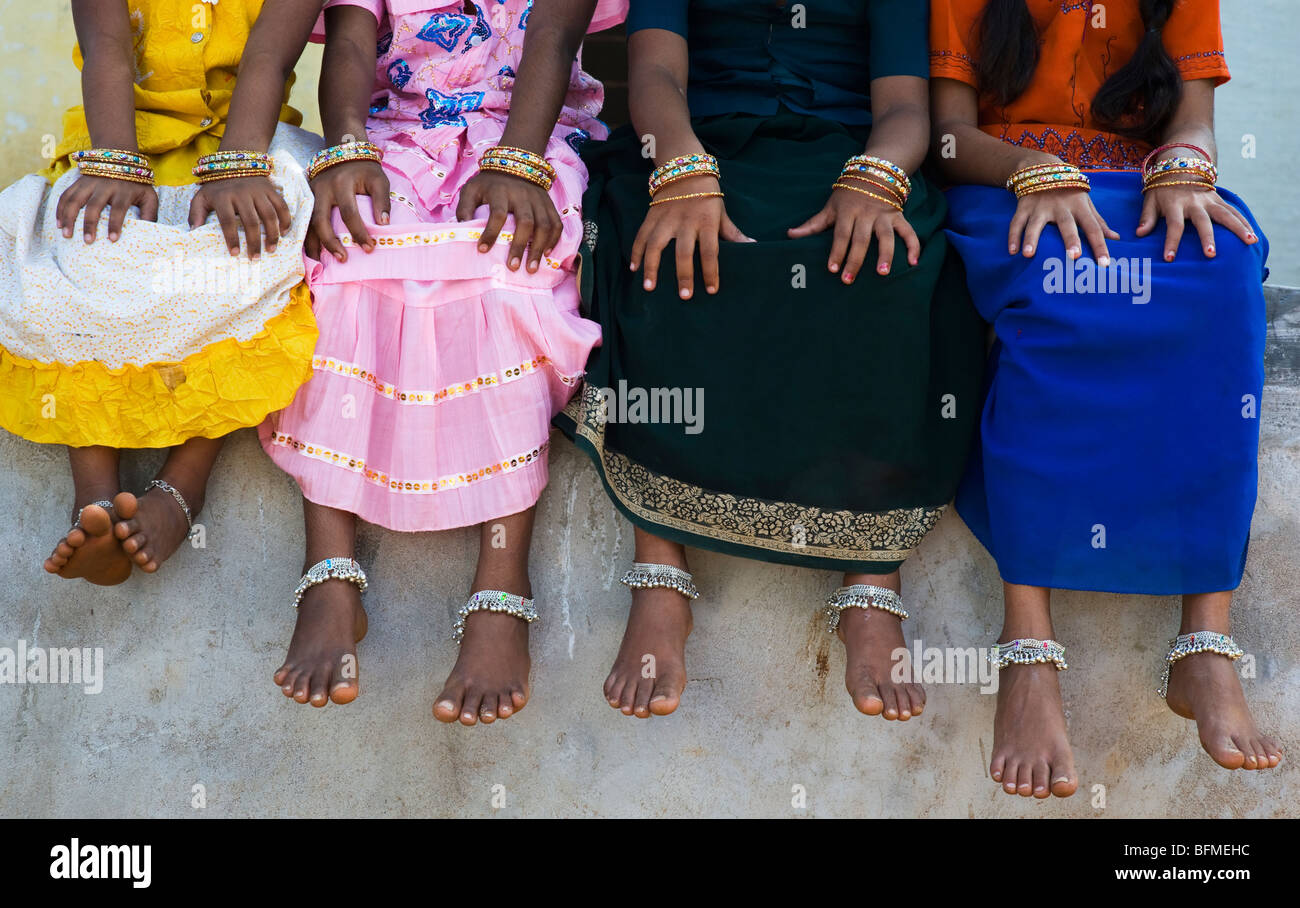Four Indian Girls Legs, Arms And Feet With Ankle Bracelets And Glass  Bangles Sitting On A Wall In An Indian Village