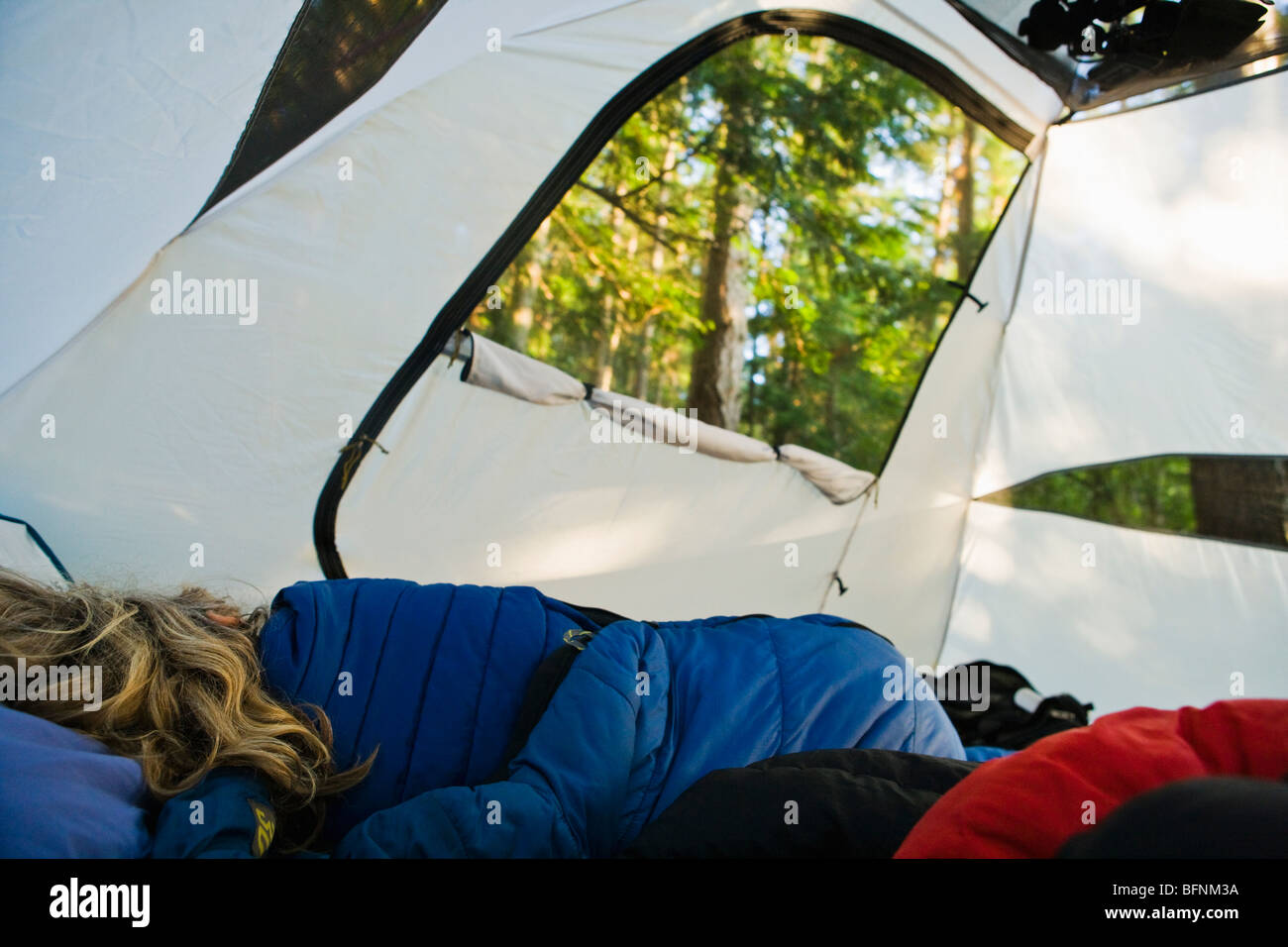 A woman sleeping in a tent in a forest on Lopez Island Washington USA & A woman sleeping in a tent in a forest on Lopez Island Washington ...