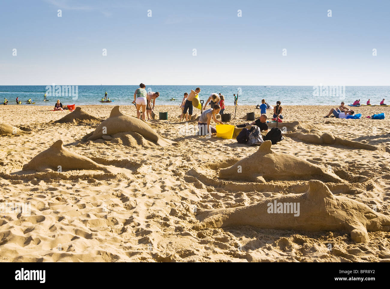 families making sand sculptures of dolphins on boscombe beach