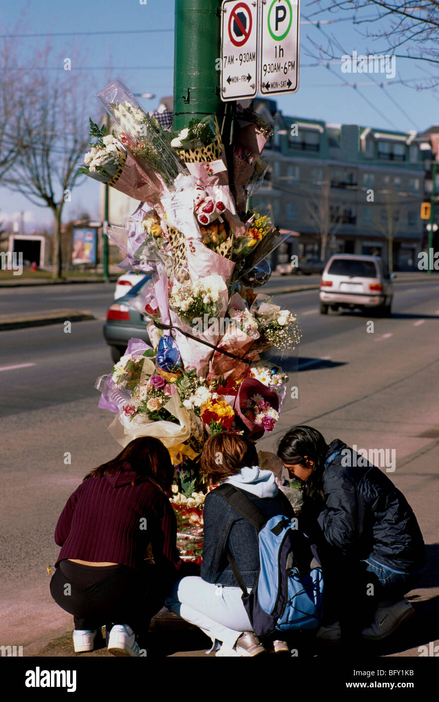 stock photo teenage girls at roadside memorial shrine of flowers for victims killed in fatal car accident vancouver british columbia canada