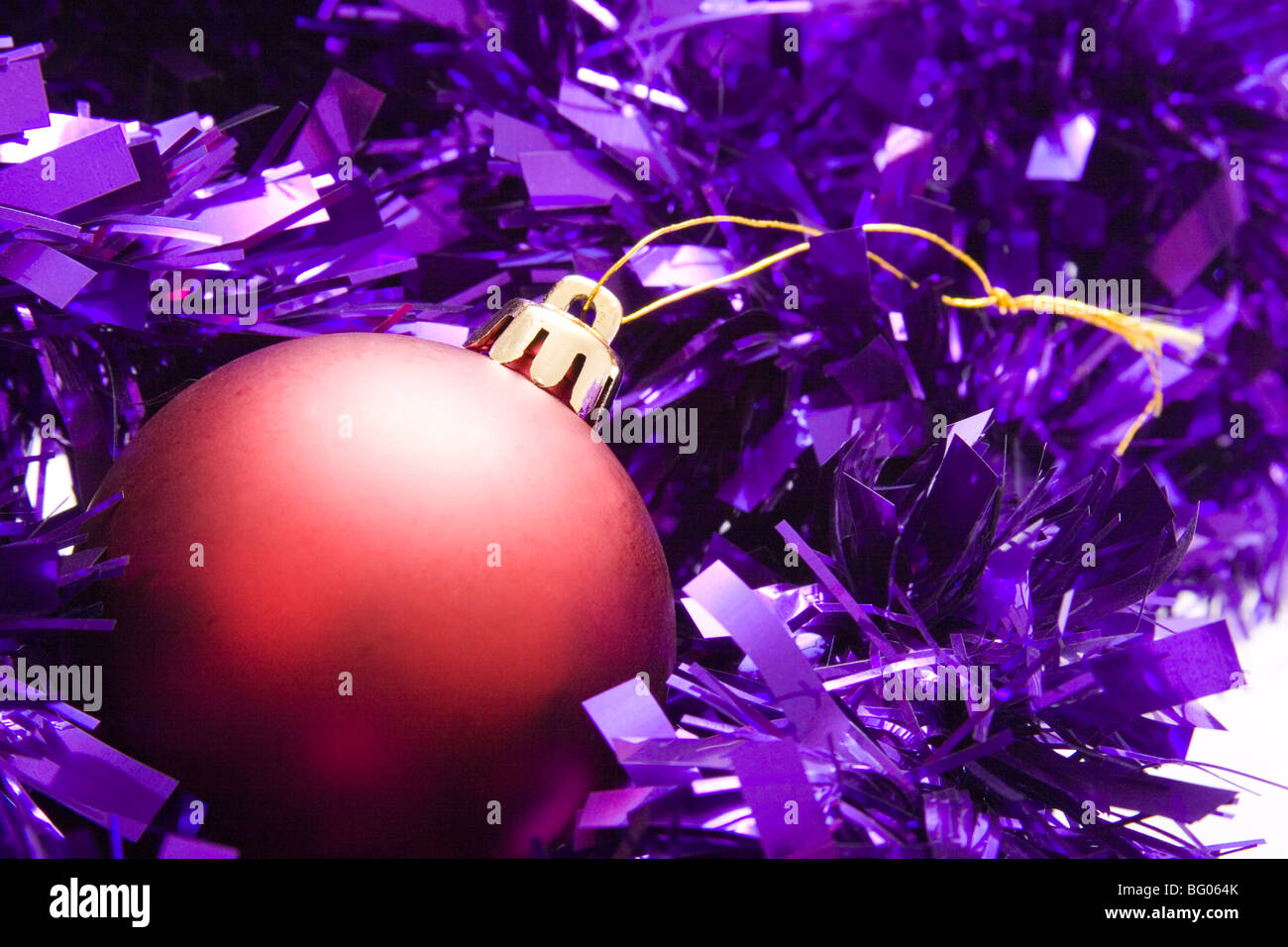Purple and red christmas decorations - Stock Photo The Essence Of Christmas Decorations A Red Bauble In Purple Tinsel