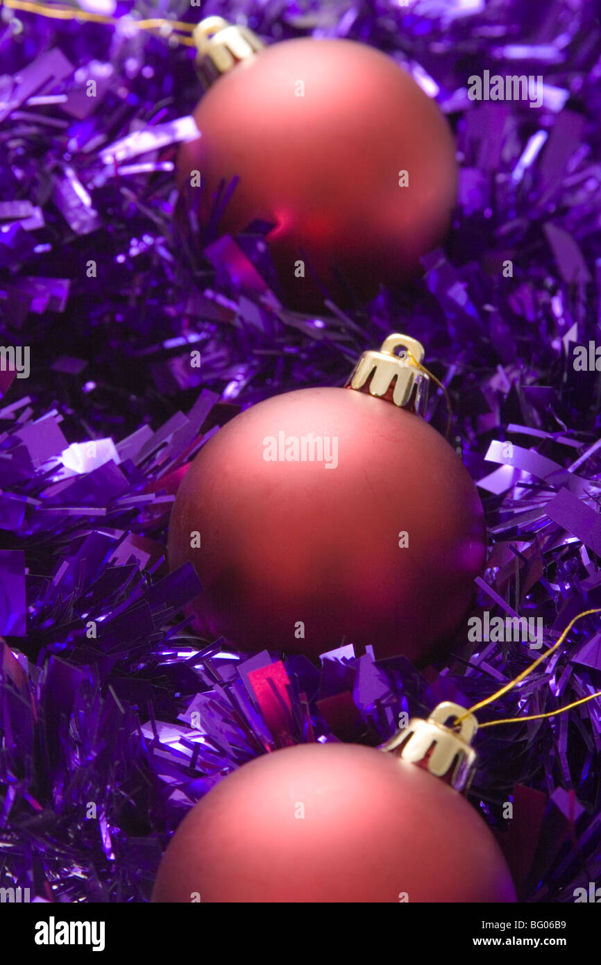 Purple and red christmas decorations - Stock Photo The Essence Of Christmas Decorations Three Red Baubles And Purple Tinsel