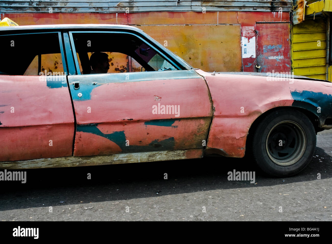 A rusty and damaged American classic car from 1970s, used as a ...